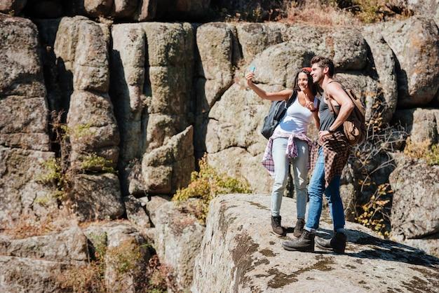 Jeune couple heureux prenant selfie dans les montagnes avec smartphone
