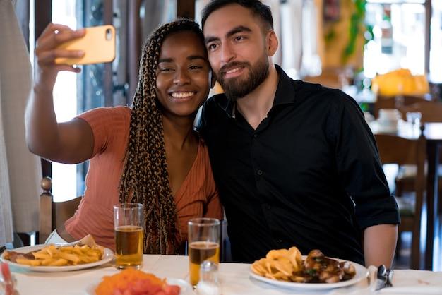 Jeune couple heureux prenant un selfie avec un téléphone portable tout en profitant d'un rendez-vous dans un restaurant.
