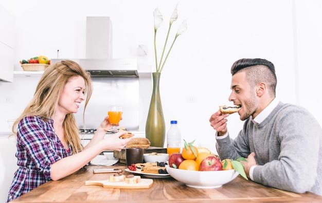 Jeune couple heureux, prenant son petit déjeuner le matin