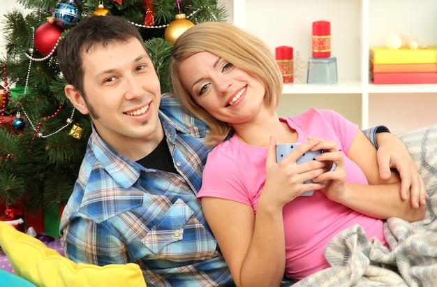 Jeune couple heureux près d'un arbre de noël à la maison