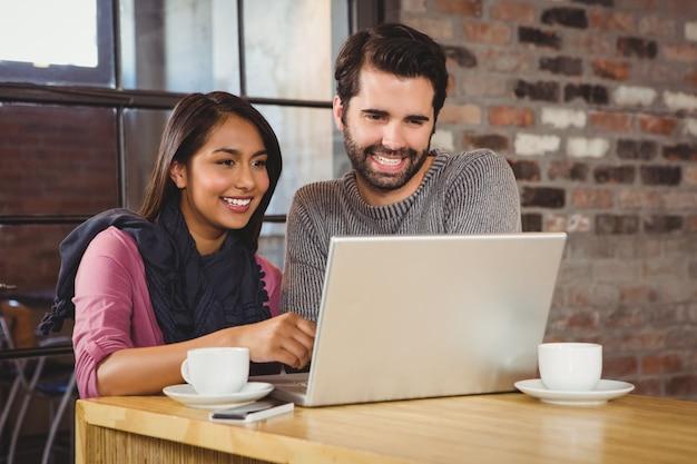 Jeune couple heureux en regardant un ordinateur portable