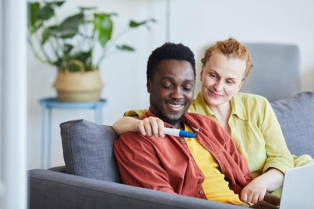 Jeune couple heureux regardant un test de grossesse assis sur un canapé dans le salon à la maison