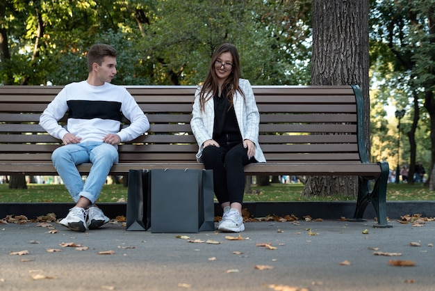 Jeune couple heureux reposant sur un banc. guy et fille après des achats réussis. je viens de me marier avec des sacs de courses noirs.