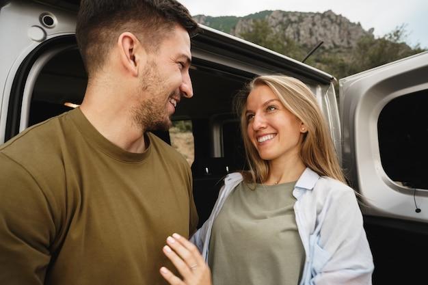 Jeune couple heureux sur un road trip assis dans le coffre de la voiture