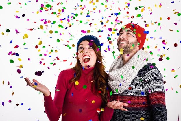Jeune couple heureux robes avec des vêtements d'hiver sur fond blanc