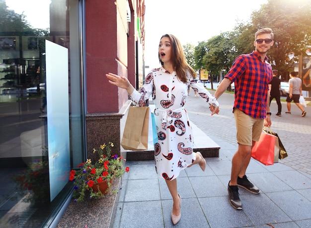 Jeune couple heureux avec des sacs à provisions dans la ville.