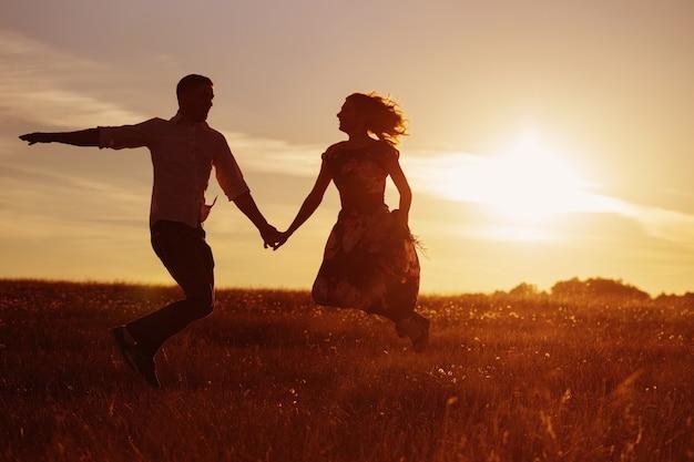 Jeune couple heureux sautant sur coucher de soleil