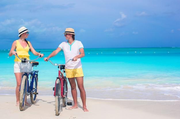 Jeune couple heureux avec des vélos en vacances de plage d'été