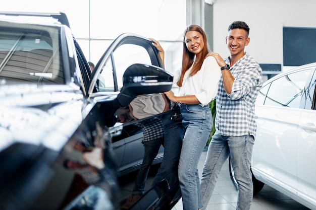 Jeune couple heureux vient d'acheter une nouvelle voiture chez un concessionnaire