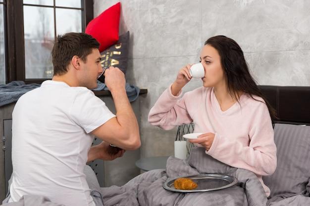 Jeune couple heureux vient de se réveiller, buvant un café et prenant son petit déjeuner au lit, en pyjama