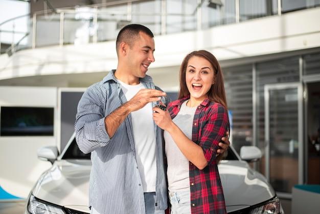 Jeune couple heureux avec voiture neuve