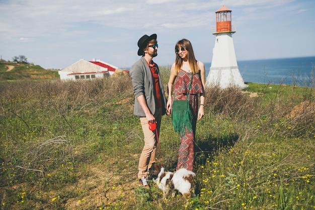 Jeune couple hipster élégant amoureux marchant avec un chien dans la campagne