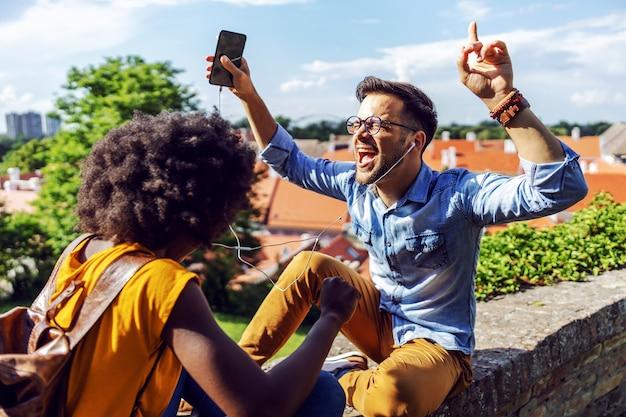Jeune couple de hipster multiculturel mignon attrayant, appréciant la musique assis sur le mur.