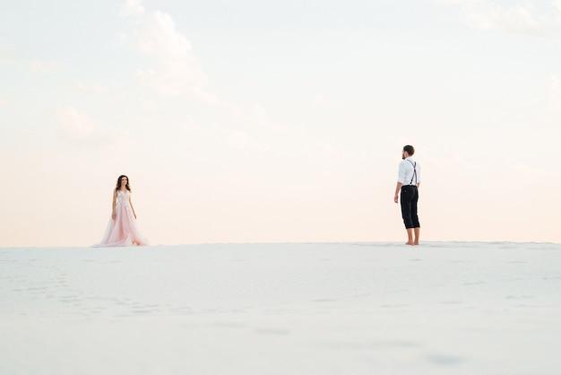 Un jeune couple, un homme en culotte noire et une fille en robe rose marchent le long du sable blanc du désert