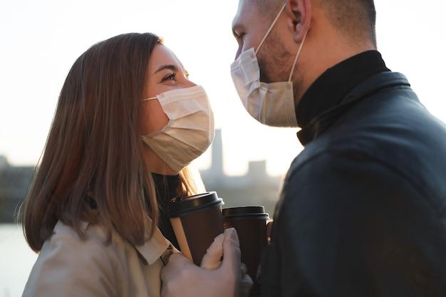 Jeune couple, un homme et une femme dans des masques médicaux et des gants
