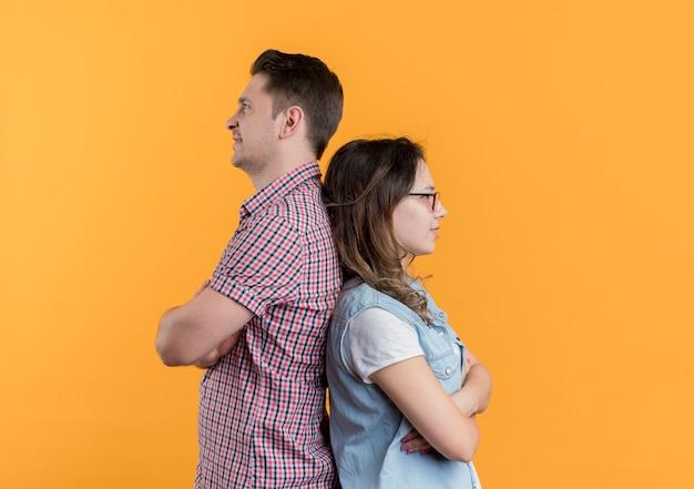 Jeune couple homme et femme dans des vêtements décontractés debout dos à dos après combat debout sur un mur orange