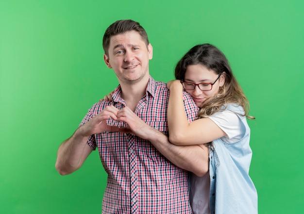 Jeune couple homme et femme dans des vêtements décontractés debout ensemble homme heureux montrant le geste du cœur sur le mur vert