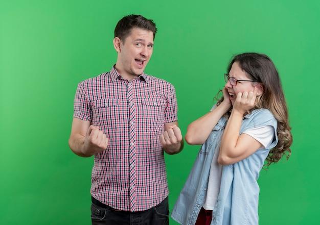 Jeune couple homme et femme dans des vêtements décontractés heureux et excité serrant les poings debout sur le mur vert