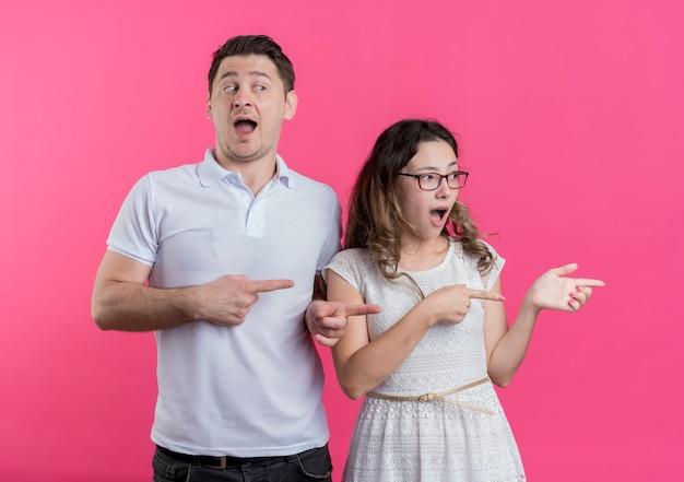 Jeune couple homme et femme dans des vêtements décontractés pointant avec les doigts sur le côté surpris et étonné debout sur le mur rose
