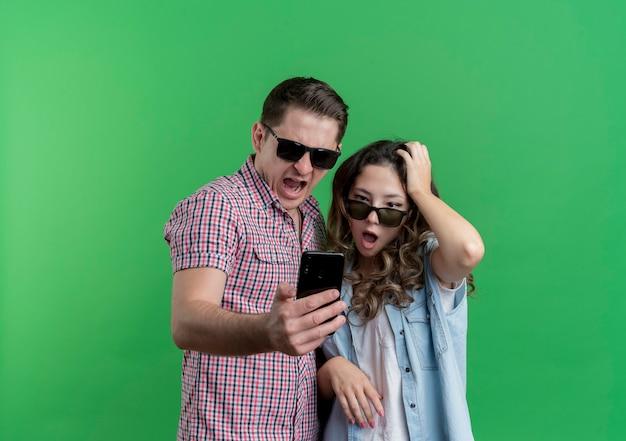 Jeune couple homme et femme dans des vêtements décontractés portant des lunettes noires en regardant l'écran de leur smartphone surpris et confus debout sur le mur vert
