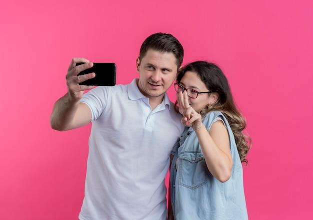 Jeune couple, homme femme, dans, vêtements décontractés, prendre, selfie, sourire, heureux, amoureux, debout, ensemble, sur, mur rose