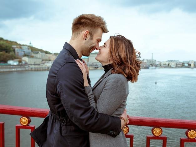 Jeune couple homme et femme debout sur le pont au bord de la rivière sur fond de paysage urbain
