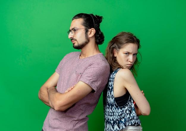Jeune couple homme et femme fronçant les sourcils tout en se tenant dos à dos pendant la lutte contre le mur vert