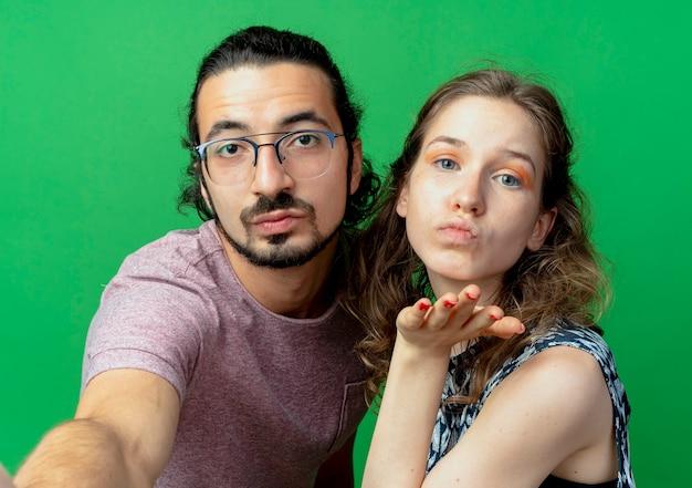 Jeune couple homme et femme heureux en amour, femme soufflant un baiser avec la main devant elle sur mur vert
