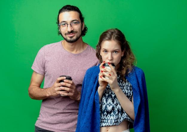 Jeune couple homme et femme, heureux en amour tenant des tasses de café debout sur un mur vert