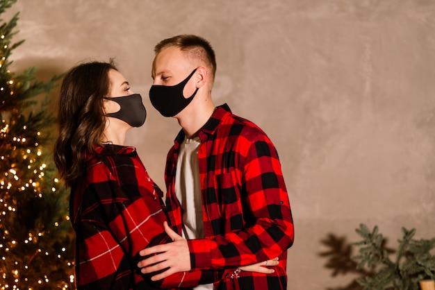 Un jeune couple homme et femme en masques médicaux jetables sous un arbre de noël.