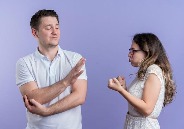 Jeune couple homme et femme se quereller femme avec les poings regardant avec visage en colère à son petit ami alors qu'il montrant panneau d'arrêt debout sur le mur bleu