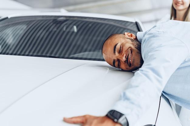 Jeune couple homme et femme serrant leur nouvelle voiture dans un magasin de voiture se bouchent