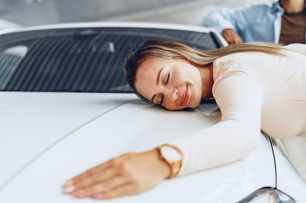 Jeune couple homme et femme serrant leur nouvelle voiture dans un magasin de voitures