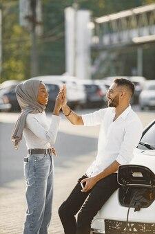 Jeune couple homme et femme voyageant ensemble. arrêtez-vous à la station de recharge de voiture.
