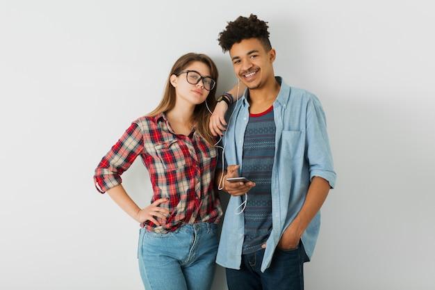 Jeune couple, homme noir hipster, fille de race blanche sur fond blanc isolé, tenue élégante, amis s'amuser ensemble, écouter de la musique sur les écouteurs, tenant un téléphone intelligent, souriant, heureux