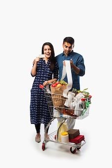 Jeune couple indien avec caddie ou chariot plein d'épicerie, de légumes et de fruits. photo pleine longueur isolée sur mur blanc