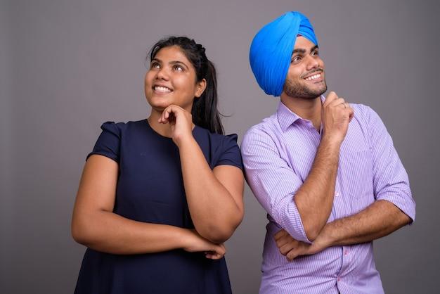 Jeune couple indien ensemble et amoureux contre mur gris