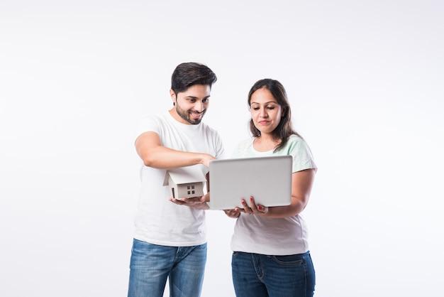 Jeune couple indien de famille choisissant une nouvelle maison en ligne, recherche de biens immobiliers à acheter ou à louer, maison à vendre sur écran d'ordinateur, debout sur fond blanc