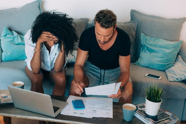 Jeune couple interracial dans le canapé a souligné des problèmes financiers en faisant des calculs avec du papier