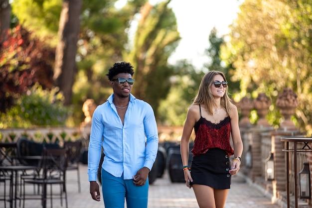Jeune couple interracial marchant ensemble sur la terrasse d'un restaurant. homme noir et fille blanche.
