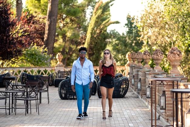 Jeune couple interracial marchant ensemble sur la terrasse d'un restaurant.