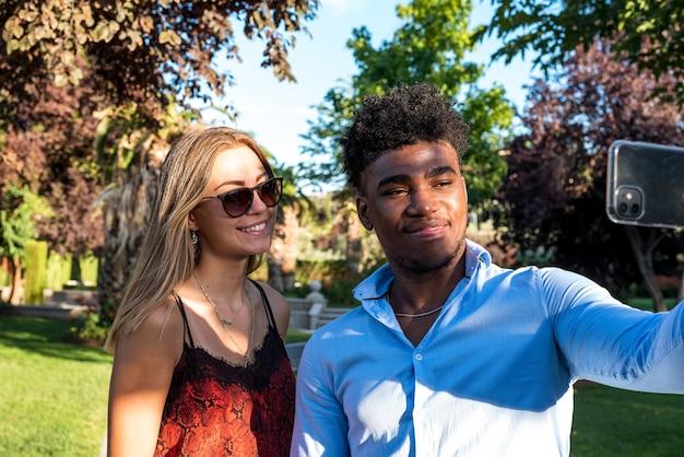 Jeune couple interracial prenant un selfie dans un parc avec son téléphone portable.