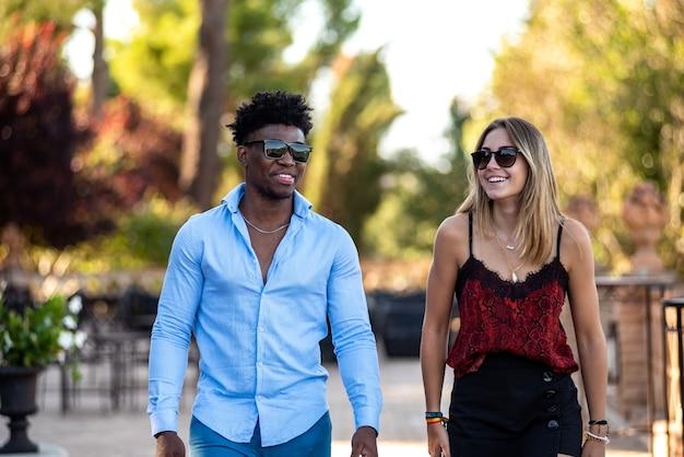 Jeune couple interracial s'amusant en marchant. homme noir et fille blanche.