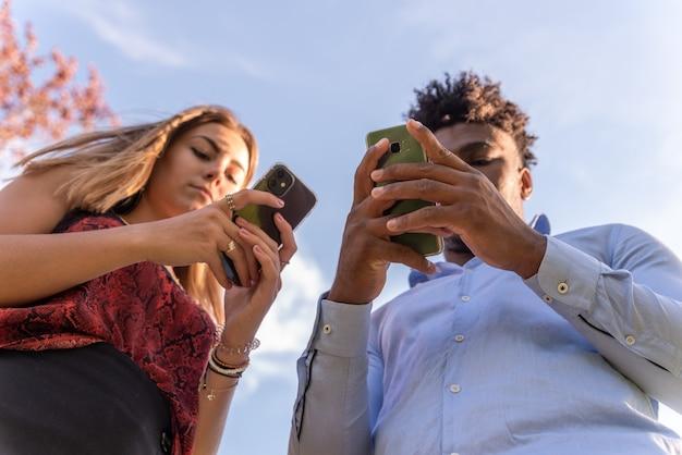 Jeune couple interracial utilisant leurs téléphones portables. vue d'en bas. fond de ciel bleu.