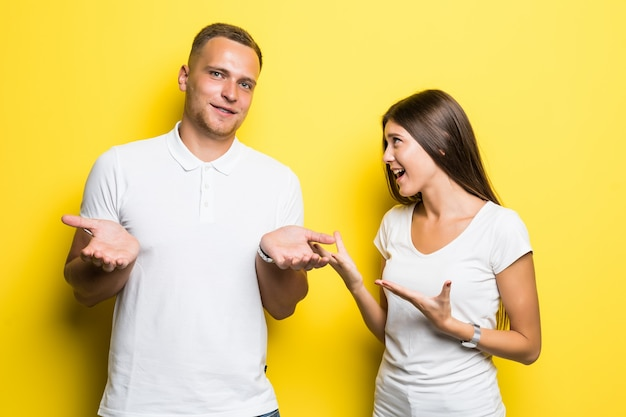 Jeune couple isolé sur fond jaune ont une conversation ensemble habillé en t-shirts blancs