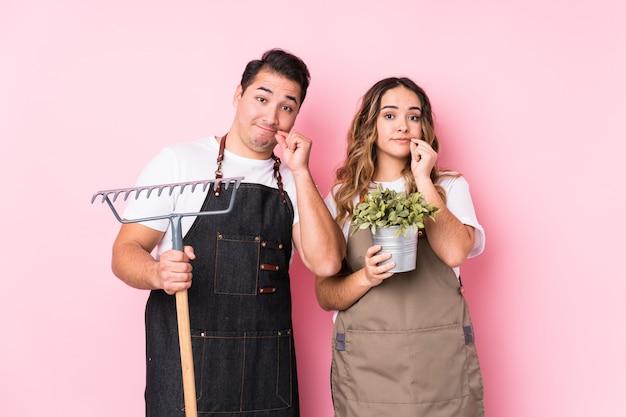Jeune couple jardinier avec les doigts sur les lèvres gardant un secret.