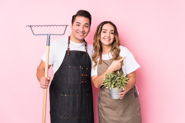 Jeune couple jardinier isolé souriant et pointant de côté, montrant quelque chose à l'espace vide.