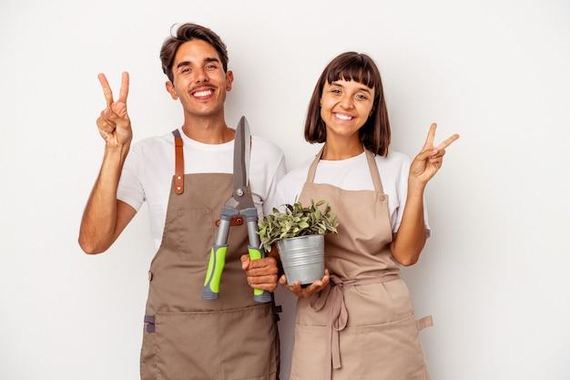 Jeune couple de jardinier métis isolé sur fond blanc joyeux et insouciant montrant un symbole de paix avec les doigts.