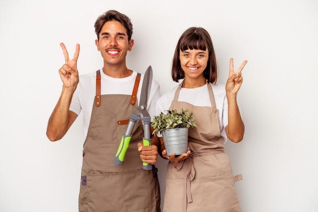 Jeune couple de jardinier métis isolé sur fond blanc montrant le numéro deux avec les doigts.
