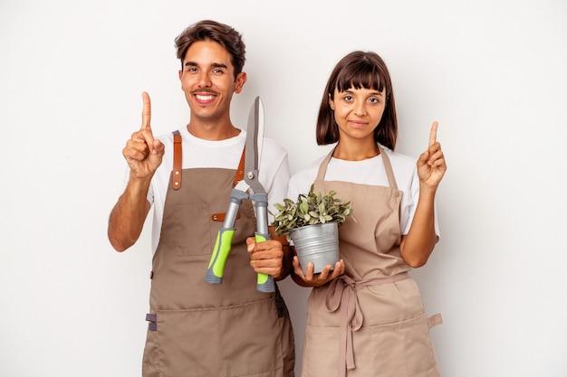 Jeune couple de jardinier métis isolé sur fond blanc montrant le numéro un avec le doigt.